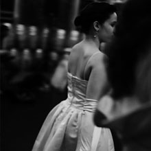Dancer in ball gown walking through crowd