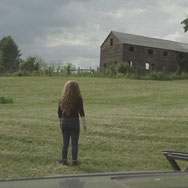 Girl facing a run down scary barn