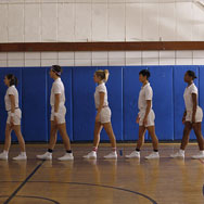 6 dancers lined up inside a gym