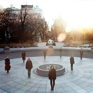 Nine people standing spread out in Washgington Square Park in winter attire