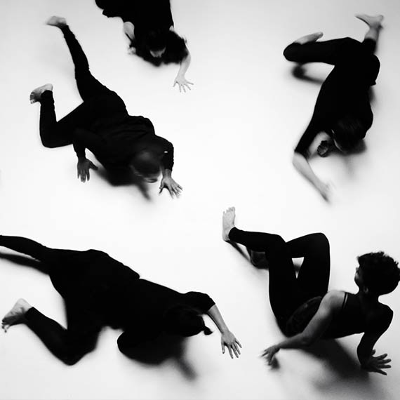 Dancers dress in black crawling towards singer in music video